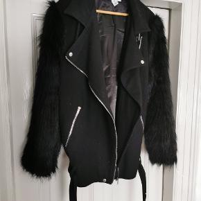 Oversize hoftelang jakke med faux pels ærmer og bælte detalje i bunden.
