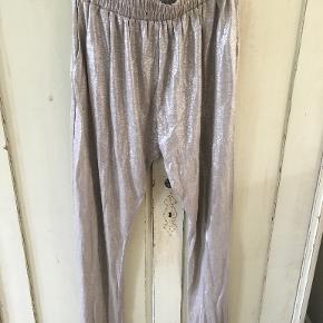 Fede guld/beige-bukser fra Heartmade/Julie Fagerholt i str L/40. De er brugt 3 gange. Der er elastik i livet og udstrakt måler den ca: 2x65 cm. Indvendig benlængde: 92 cm. De er lavet af 100% linen. BYTTER IKKE. Sælges for 500 kr. Se også mine andre annoncer!!!