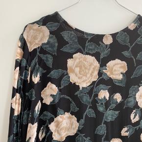 Smuk kjole fra Ganni model stort blomsterprint.  Materiale: Viscose. Flæsedetaljer i bunden og trekvartærmer. Brugt få gange, fremstår som ny. Passes af str. M-L