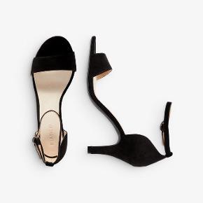 """Helt nye sorte sandaler, aldrig brugt. Stilethæl, hælhøjde 8 cm. Overdel: polyester, sål: syntetisk. Sælges stadig på Bianco's hjemmeside som """"En strop sandal"""", nypris 399."""