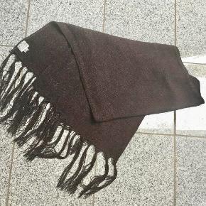 Lækkert, groftvævet tørklæde fra MASAI. Mål : 45 cm. X 145 cm. Lange frynser. Har enkelte trådudtræk, men også lidt synlige trådhæftninger som det er født med.  Brugt få gange. Farve: Mocca / mørk brun Oprindelig købspris: 450 kr.  Sender gerne på købers regning : DAO 39,-