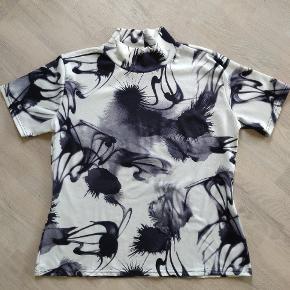 Varetype: t-shirt Farve: sort, hvid og lidt grå   Mønstret bluse med halskrave. Halskraven sidder løs, blusen er str. Xl, men er mere en str. L.