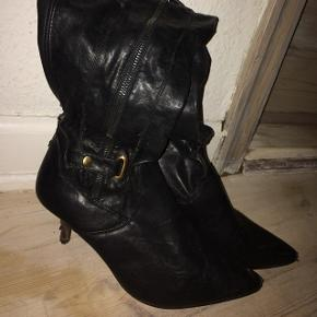 Lange sorte støvler. Slidt i syningen bag på og lidt foran, ellers pæn i stoffet. Meget smal hæl. Hælen er 7 cm. Selve støvlen er 42 cm.