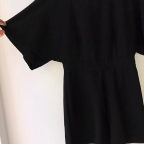 Elegant sort buksedragt med bånd rundt og sølvspænde bagpå. Flot brede på ærmerne og ben.  Kom gerne med et bud.