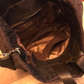 Tasken er  brugt som arbejdstaske i en kortere periode. Tasken Er i fin stand. Tasken er rummelig og egner sig godt som en skoletaske eller arbejdstaske. Tasken er i stofmateriale.
