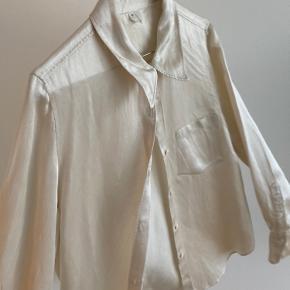 Hvid lækker skjorte, der med sit skinnende look er god til et par jeans - evt. med et par hæle eller sneakers.  Er brugt et par gange, men er god som ny.