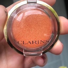 Lipgloss i farven Sunset Coral. Transparent fersken med guld.  Aldrig brugt.