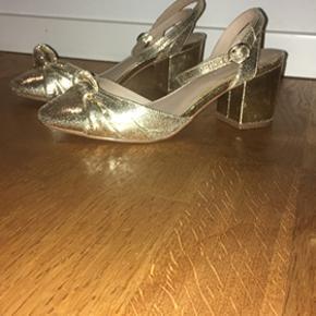 Fine, skinnende sandaler med lille hæl på ca. 3-4 cm. Spidsen er lukket og der er fint med plads til også lidt bredere fødder. Ovenpå er der en pynteknude. Skoene fastgørres ved at snørre remmene på kryds rundt om anklen og låses i spændet.  De er  perfekte til at peppe et hvilket som hælst outfit op til fest eller give lidt glimmer til hverdagen.