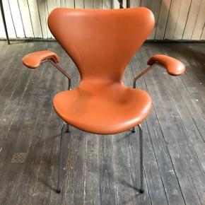 Kom med et bud!  Arne Jacobsen 7'er stol i cognac med armlæn. Aldrig brugt og derfor fast i ryggen. Lille mærke på stolen, tror dog det kan komme af. Se billede (den lille sorte plet på 2. billede -det andet er et midlertidig mærke af at have været stablet med anden stol).   Koster lige under 10.000 fra ny. Kvitteringen haves ikke længere, men der er stempel under stolene, se billede.  Jeg overvejer at sælge, da jeg aldrig har fået den brugt.   Mp 5000