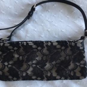 Super fin lille blonde taske, clutch med strop der kan justeres. Sort og beige