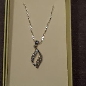 Halskæde i sølv (ITALY 925), 45 cm lang, vedhæng i børstet sølv (925) med zirkoner,  måler 1.2 cm i højden og er 0.8 cm på det bredest sted.  Halskæden leveres i gaveæsker og kan sendes for 10 kr med Post Nord, almenlig brev.