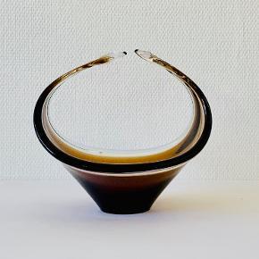 Utrolig smuk stor figur/kurv fra Paul Kedelvs organiske Coquille serie. Designet for Flygfors i 1959. Udført i brunt glas overtrukket med klart glas ved brug af den venetianske sommerso teknik. Et smukt stykke kunsthåndværk der vil pynte i ethvert hjem eller samling. Længde: 11 cm Højde: 12,5 cm