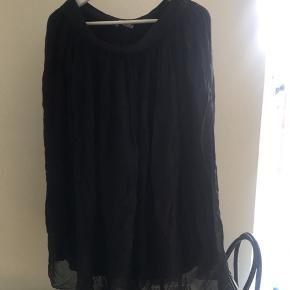 Let kjole med to lag stof - et flagrende let stof og indre tætsiddende, let stof. Elastik i talgen.
