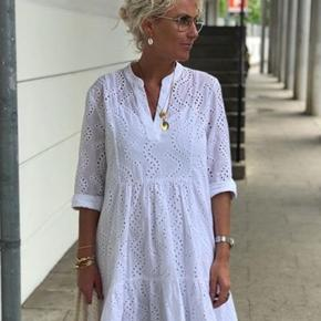 Absolut et MUST HAVE. Den fineste kjole fra Love&Divine, i et smukt broderi anglaise mønster i hvid og med feminine snit. 100% Viskose. Falder lidt længere bagpå, således at kjolen er længere bag til. Underkjole følger med kjolen. Nem at style både til hverdag og fest. Helt ny og med mærke på endnu