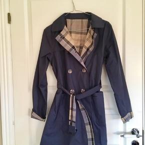 Lækker vandtæt vendbar Barbour dame trenchcoat (stort set ikke brugt). 100 % polyester. Mørkeblå eller frisk ternet afhængigt af dagens humør eller din beklædning!