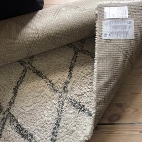 Lang luvet ryatæppe fra Jysk. I råhvid med grå stribe.   Brugt men i pæn stand. Ville nok give det en tæpperens. Maskine kan lejes fra 99 kr i døgnet.   160 x 230 cm.   Skal afhentes i Hellerup.