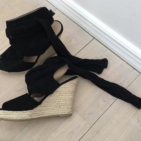 Super flot sandal i sort ruskind m. kilehæl  Båndet bindes op ad benet.  Mærke: Belluci