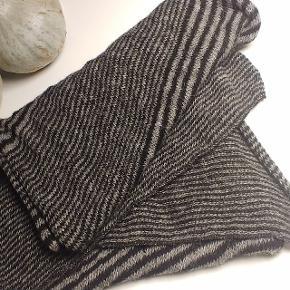 Islandsk uldtørklæde fra VARMA med blandede striber.Passer både kvinder og mænd.  Længde: ca.220 cm  Bredde: ca.50 cm  Vægt: ca.230 g  Farvekombination: sort-grå  Model: var-064  Materiale: 100% islandsk uld  håndvask  Producent: VARMA  Fremstillet på Island  Islandsk design
