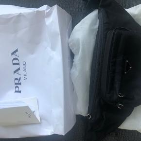 Helt ny Prada bæltetaske  Alt originalt som kvittering, dustbag og kvit medfølger.  Kan sendes eller afhentes i Vejle  Mp:3500 Bin:4800
