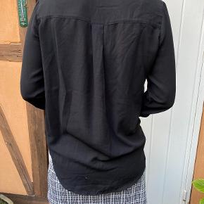 Skjorte med detalje på ryg og på skuldrene med knapper.   Varen kan afhentes i Helsingør centrum, eller sendes med DAO via trendsales' handelssystem på købers regning.   Skriv gerne hvis du ønsker flere billeder af tøjet eller har spørgsmål.   Husk at tjekke profilen ud for mere tøj ;)