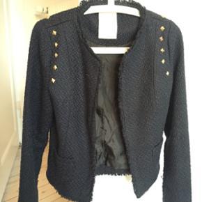 Blazer/jakke fra Nümph str. 36. Mørkeblå i vævet tykt materiale og guldnitter på skuldrene. Brugt få gange. Nypris 600.