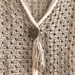 Skovhuus lækker hulmønstret strikcardigan str M . Brystmål 2 x 43 cm og længde 60 cm. Matr 15%bomuld, 80% acryl og 5 % polyester.