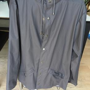 Rains Regnjakke i str. S - lige over knæ-længde.  Normalpris 600 kr.  Har en lille skramme på venstre lomme, som skal ses tæt på.
