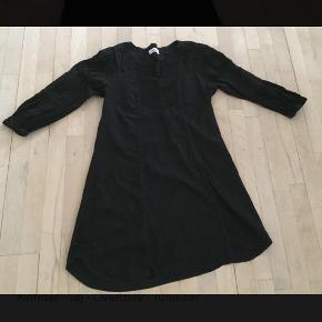 """Lang bluse/top med 3/4 ærmer, som har elastik forneden. Med """"broderi"""" foran ved bryst. Længde: ca 86 cm."""