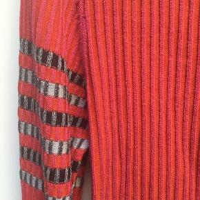 Silkestrik i pink og rød m. sort/grå mønsterdetalje på ærmerne. Brystmål ca 100cm Længde ca 60 cm