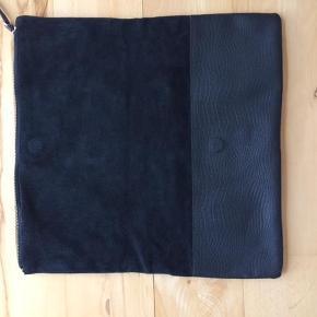 """Varetype: clutch Størrelse: 37x38 Farve: Sort Oprindelig købspris: 900 kr.  smuk ny clutch I sort læder/ruskind. Den har lynlås øverst og lynlåslomme halvvejs, på den ene side. Lukkes halvt ned med magnet syet ind i læderet.  Måler 38x37 og 37x19 når den er """"klappet sammen"""".    Bud fra 350+ ingen bytte tak"""