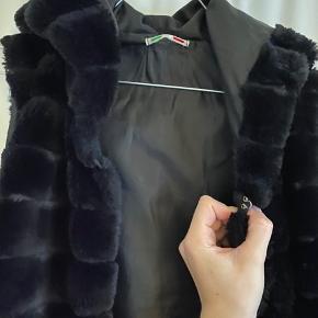 Faux Fur. Købt i en butik Barcelona, derfor er mærket ukendt.  Brugt få gange, enten uden på en trøje eller brugt udenpå en almindelig sort jakke.  Ingen brugsspor, har påsat en hægt så man kan lukke den foroven.
