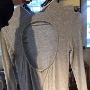 Kjolen er tætsiddende med åben ryg og slids bagpå. Den er brugt en gang:)