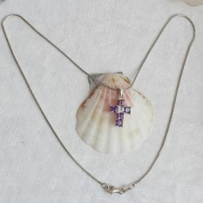 Sølvhalskæde med kors vedhæng med lilla zirkonia sten. Kædens fulde længde er 42,5 cm, den er stemplet 925 og ANY. Kors vedhæng er inkl. øsken 2,4 cm og er stemplet 925.  Prisen er fast.  👉 Tryk på mit profilbillede for at finde flere smykker med beskrivelser og priser 🍀