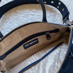Mega fin navyblå taske fra Karl Lagerfeld, med massere af plads og super pæne detaljer indeni🤩  Der er 3 små lommer indeni, og en udenpå som er ok stor. Der er nok plads til at en MacBook kan stå på højkant i den. Lukkes med lynlås.  Aldrig brugt, købt i USA for $170, hvilket svarer til ca 1.125kr   Kan sendes eller afhentes i Aalborg-området eller Aarhus   Obs: er en smule mørkere i virkeligheden end på billede