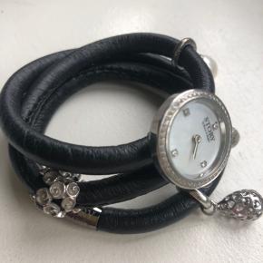 STORY by Kranz og Ziegler.  Sort armbånd med fem forskellige vedhæng inklusiv et lille ur (uret går ikke).