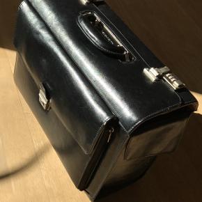 God rummelig taske i sort læder. Der er lås med kode.