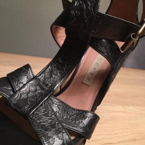Flotte sandaler / heels med wedge   Sort skind med prægning. Plateau på 4 cm og hæl på 12 cm.