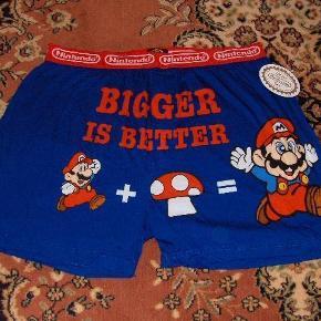 NINTENDO BOXER SHORTS MED MARIO - STR. XL  Seje boxer shorts med Mario og den lidt frække tekst 'Bigger is Better'. Billedet med mario er både foran og på 'bagdelen'. Teksten er foran. Størrelsen er 'XL' (USA str. 40-42) og det er 100% bomuld.  Længde ca. 46 cm. fra top af elastik/liv til bund/lår  Elastik i liv: ca. 92 cm. (hele vejen rundt). Bemærk at elastikken er præget med 'Nintendo' hele vejen rundt (hele 4 CM bred!)  Der er det officielle Nintendo Seal - både med emblem samt i det indsyede mærke.  Start en trend - hav Mario boxer short på når du spiller på din N64, Gamecube, WII. Eller på stranden til sommer!    Forsendelse:  GLS Pakke med sporing (du afhenter selv i din lokale GLS Pakkeshop): Kr. 35 eller Post Nord alm. brev (250-500 gram): Kr. 45 eller Post Nord Pakke med sporing: Kr. 80 + (Kr. 60 uden omdeling).  Vi tager forbehold for stigninger i porto priser!  Kan evt. afhentes i 2670Greve Syd.  boxer Farve: Blå