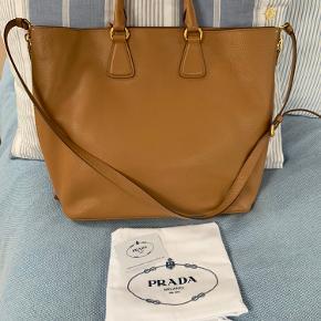 Super skøn taske fra Prada sælges (bytter ikke ) brugt få gange og er i virkelig god stand.  Tasken hedder Vitello Daino Tote Bag og farven er Beige/Camel.  Kan bruges som håndtaske og cross over.  Strop måler ca 109 cm. Og kan forlænges med ca 12 cm.  Håndtag ca 35 cm.  Tasken mål : Brede 45 cm. Kan udvides med ca 20 cm. H 35 cm Bund 15 cm.  Interiør fuldstændig rent og nyt.  Kvittering medfølger  Køber betaler fragt