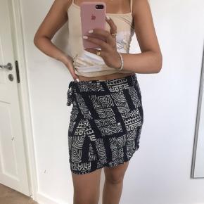 Blå nederdel med hvidt mønster. Binder i siden. Er flot uden på bukser  Sommer strand bindenederdel wrap kort