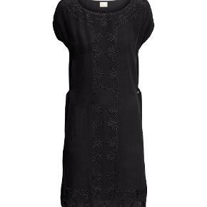 Bytter ikke. Eksklusiv porto. Varetype: Kjole/tunika, silke Utrolig smuk og meget elegant sort silkekjole/tunika fra H&M, str. 40.  Der er bindebånd i siderne, slidser i begge sider, kjolen er dekoreret med smukke bånd front og ved slidserne.   Længde fra nakke og ned 94 cm.  For og bag stykke ved bryst linjen, 104 cm Omfang af kjolen forneden 118 cm.  Slidser i begge sider, længde 23 cm. Kjolen/tunikaen er let gennemsigtig.  Kjolen er ny.  Den hænger i dragtpose.  Kommer fra et ikke ryger hjem.