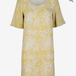 Lækker knælang sommerkjole fra Stine Goya. I en let viscose kvalitet, perfekt til sommeren.   Farver: lys gul creme beige grå ... Lukkes med en lille guldknap i nakken.  Brugt enkelte gange.  Fra dyre- og røgfrit hjem.