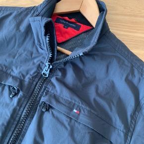 Denne klassiske mørkeblå jakke er for lille til min mand, så hænger bare i skabet. Vind- og vandafvisende. God overgangsjakke. Købt i Magasin.