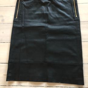 Meget lækker nederdel i blød skind og flot guldknapper. 55 cm lang