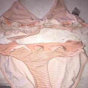 Fin bikini til pige str 146/152  Pæn stand men har dog 2 små prikker ved ikke hvad der er kommer fra