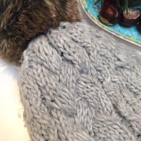 Strikket hue med med kvast i falsk pels. Den største børnestørrelse, som sagtens fitter et lille voksenhoved