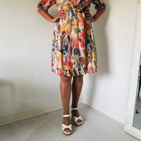 Smuk kjole str. S fra Vero Moda med abstrakt mønster i farver som rød, orange, blå og grøn. Fine flæser ved halsen og skæring under brystet. Ærmerne er 3/4 lange og har elastik i enderne. Underkjole i lys beige. V-udskæringen er dyb, og derfor er kjolen vist med en lille top under på billedet. Længde fra skulder er 92 cm, og brystmålet er 78 cm. Fremstillet af polyester.