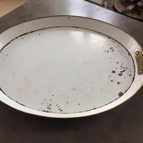 Smuk antik, oval metalbakke i original råhvid farve med messingkanter og hanke. Super fin patina. 1800-tallet. Købt på antikmarked i udlandet. Bakken har været brugt som bakke(bordplade) på en puf. Patinaen er fra den blev købt. Mål : længde 65cm x bred 53cm x højde 5cm. Pris + Porto(DAO), gerne mobilpay eller TS-handel +5%