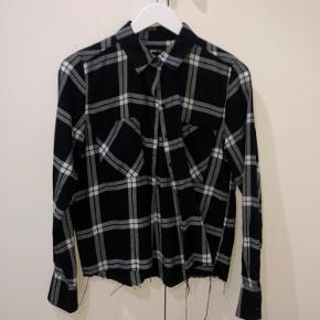 Skjorten er sort, hvid og grå.  Skjorten er klippet forneden.  Den er true to size.