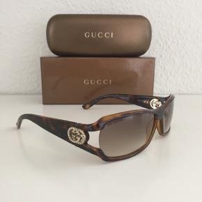 Super fede Gucci solbriller med tonede glas samt det klassiske gg-logo i guld på stængerne der er besat med strass sten som virkelig giver solbrillen et eksklusivt look 🤩 God og pæn stand, dog mangler der 3 små sten på venstre side. Kvittering haves. Model GG 3031/Strass  Nypris: 2.500 Mp: 1.200
